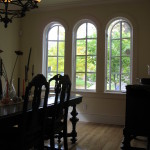 Dining table with three arched windows beyond
