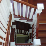 Cherry stairs with a painted wood railing decend form second floor to basement