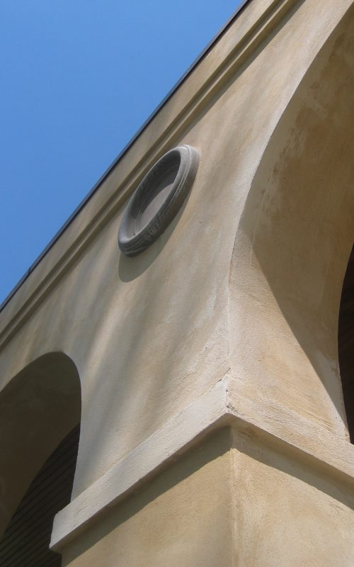 Stucco arches and stone medallion on porch